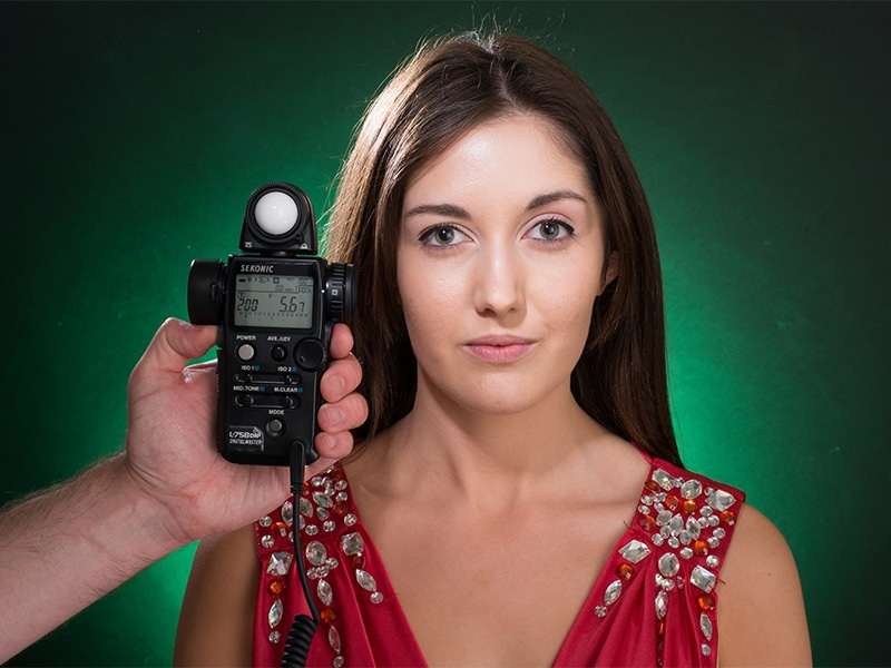A portrait shot of a model, taken in the studio with a dark backdrop lit with a green gel. There is a light meter taking readings to her side.